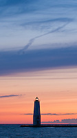 The Frankfort Pierhead Light rises into a sunset sky over Lake Michigan in Benzie County, Michigan