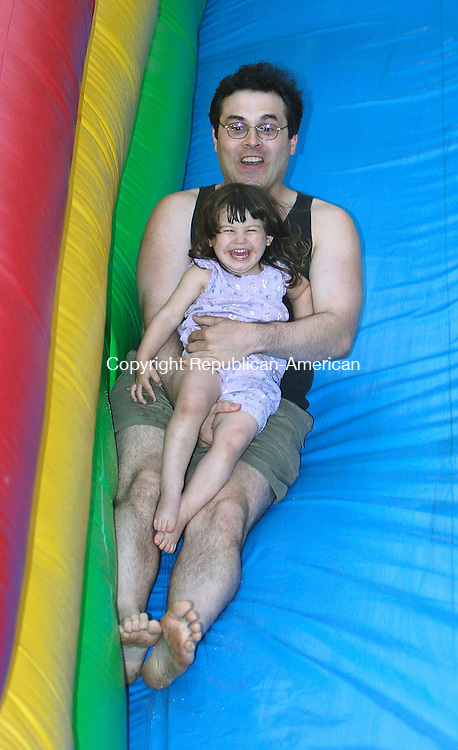 NAUGATUCK, CT - 08 June 2005 -060805BZ05- Tony Dadamo, of Naugatuck, and his daughter Sofia Dadamo, 2, enjoy a ride down an inflatable slide at the annual St. Francis Church Fair in Naugatuck Wednesday night.<br />  Jamison C. Bazinet Photo