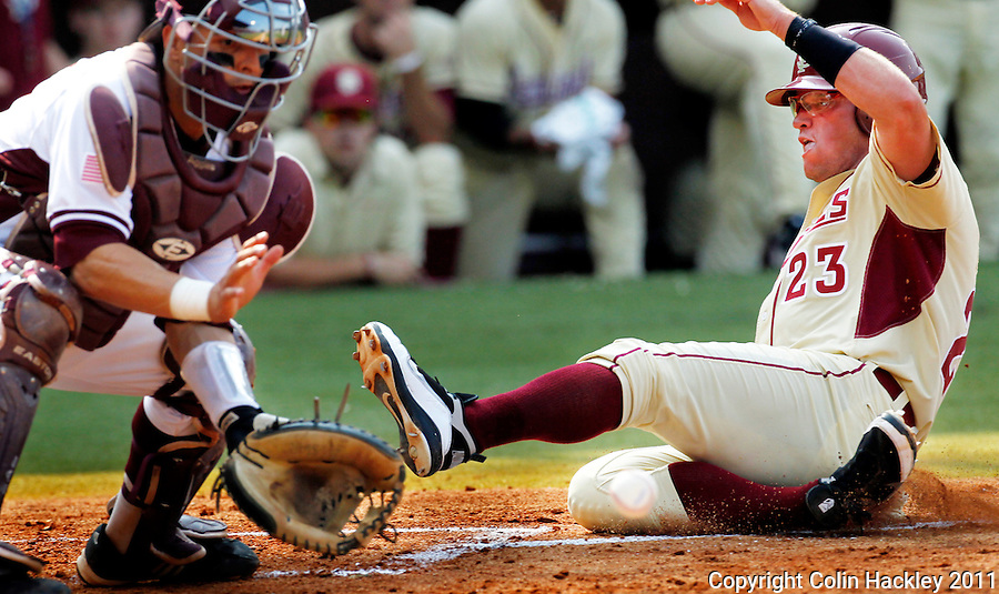TALLAHASSEE, FL 10-FSU-TAMUBASE11 CH-Florida State's James Ramsey slides by the ball and Texas A&M catcher Kevin Gonzalez to score the Seminoles third run in the first inning Sunday at Dick Howser Stadium during NCAA Super Regional action in Tallahassee. The Seminoles beat the Aggies 23-9 to stay alive in the best of three series...COLIN HACKLEY PHOTO