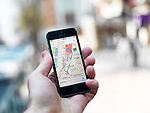 Person hand with iPhone displaying Google maps GPS navigator on streets of Tokyo, Japan.