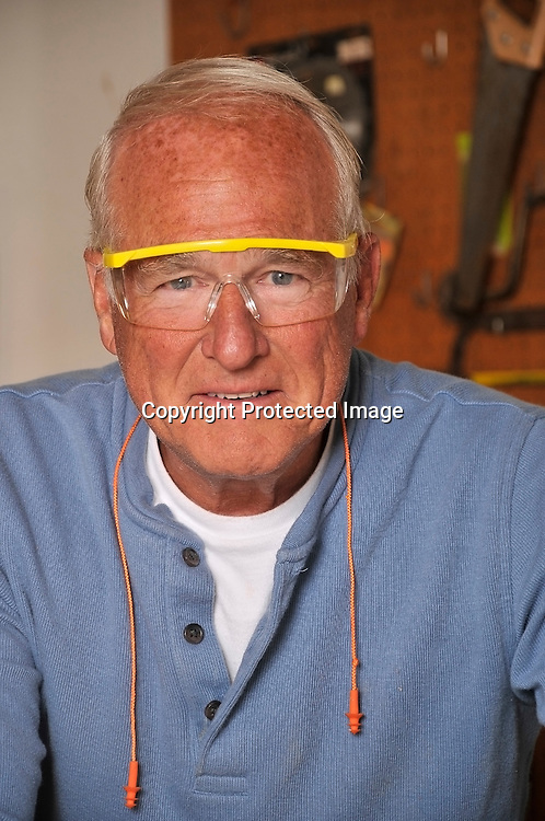 Mature Senior Retired man working in his wood shop