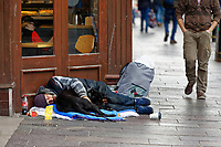 Pictured: A homeless man sleeps outside a Greggs on the junction of Church Street and St Mary Street in the centre of Cardiff, Wales, UK. Wednesday 12 June 2019<br /> Re: Homeless people living in tents in Cardiff, Wales, UK.