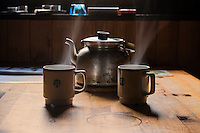 Kettle and hot cups of tea in mountain hut, Kungsleden trail, Lapland, Sweden