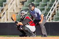 Catcher Kevin Dubler #27 of the Kannapolis Intimidators sets a target as home plate umpire Ivan Mercado looks on during the South Atlantic League game against the Hickory Crawdads at Fieldcrest Cannon Stadium on April 17, 2011 in Kannapolis, North Carolina.   Photo by Brian Westerholt / Four Seam Images