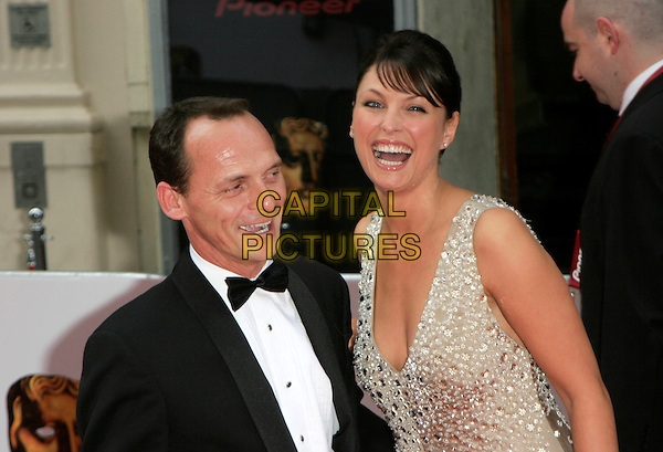 PERRY FENWRICK & EMMA BARTON.Red Carpet Arrivals at The British Academy Television Awards (BAFTA's) Sponsored by Pioneer, held at the London Palladium, London, England, May 20th 2007. .half length gold beaded cream haltrneck dress black suit bow tie funny face laughing.CAP/AH.©Adam Houghton/Capital Pictures.