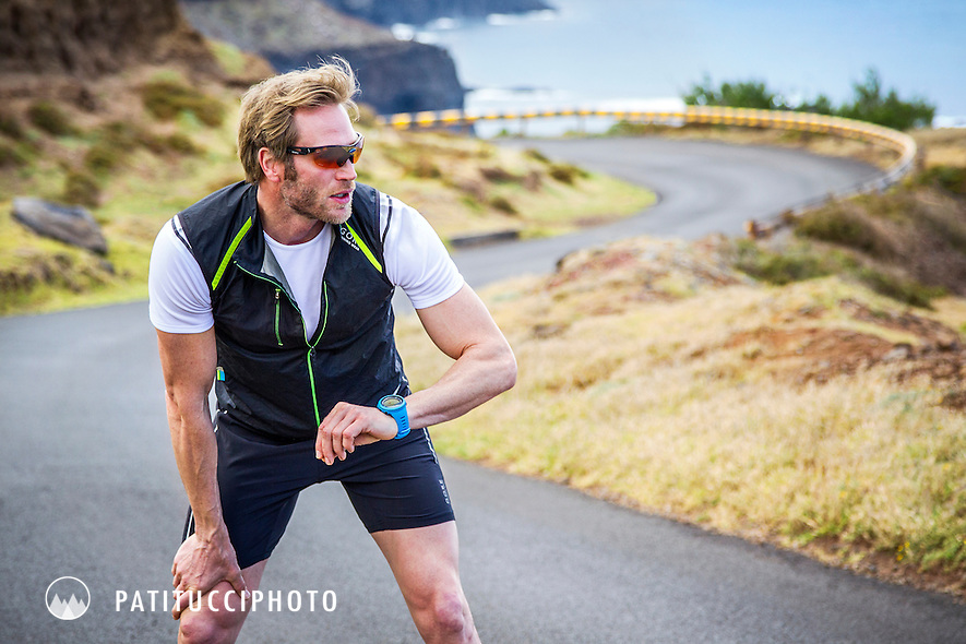 Runner taking a break and checking his watch during a road run on Madeira Island