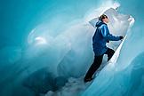 NEW ZEALAND, Franz Josef, Woman Climbing through an Ice Cave on Franz Josef Glacier, Ben M Thomas