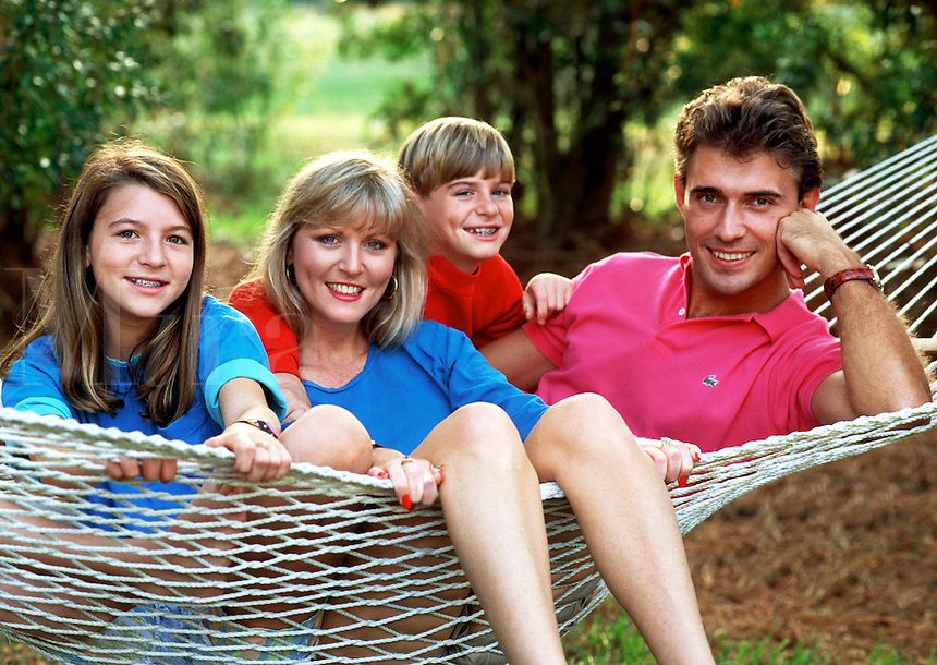 A smiling young family hanging out together in a hammock.