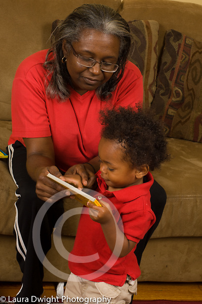 16 month old toddler baby boy with grandmother looking at books vertical