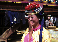 "Mosuo woman, Ai Li Zhi Ma, 19, dress rehearses for the fertility festival at her home on the edge of Lugu Lake in Yunnan. Women from the Mosuo tribe do not marry, take as many lovers as they wish and have no word for ""father"" or ""husband"". But the arrival of tourism and the sex industry is changing their culture...PHOTO BY SINOPIX"