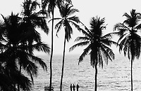 Three human figure standing in front of the sea at Kerala silhouette black and white fine art stock image.<br />