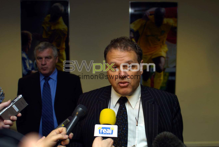 Pix: Simon Wilkinson/SWpix.com Football. Leeds United relegation story. 04/05/2004..COPYRIGHT PICTURE>>SIMON WILKINSON>>01943 608782>>..Gerald Krasner faces the press alongside Peter Lorimer sahdowed by a picture of Alan Smith after a board meeting at Elland Road today.