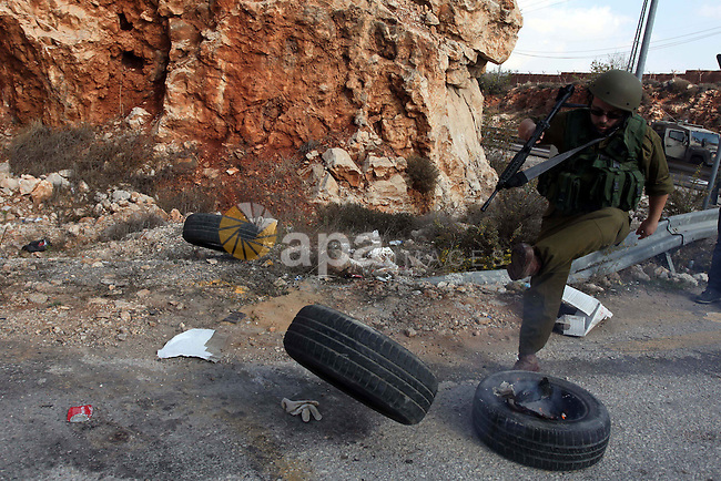 An Israeli soldier kicks a tire as Palestinian and foreign activists block the road between Ramallah and Nablus to protest against Israel's military action on the Gaza Strip, on November 19, 2012 in the West Bank village of Silwad . Israeli air strikes across the Gaza Strip killed 13 people, raising the Palestinian death toll to 90 as Israel's relentless air campaign entered its sixth day. Photo by Issam Rimawi