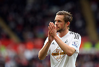SWANSEA, WALES - MAY 17: Gylfi Sigurdsson of Swansea aks home supporters to cheer on as he prepares to take a corner kick during the Premier League match between Swansea City and Manchester City at The Liberty Stadium on May 17, 2015 in Swansea, Wales. (photo by Athena Pictures/Getty Images)