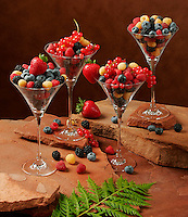 Agriculture - Mixed berries in dessert glasses on a stone surface; strawberries, red & golden raspberries, blackberries, blueberries and red currants.
