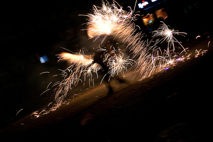 A man is dancing with fireworks for the chinese new year 2009 in Beijing.