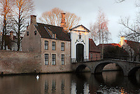 BRUGES, BELGIUM - FEBRUARY 08 : A general view of the 'Beguinage' along the canals of Bruge at sunrise on February 08, 2009 in Bruges, Western Flanders, Belgium. The 'Beguinage of the Vineyard' was founded in the first half of the 13th century during the reign of Margaret of Constantinople. A lonely swan is floating on the dark waters of the canal reflecting the cloudy sky. (Photo by Manuel Cohen)