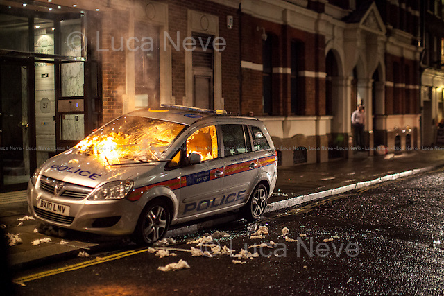 Queen Anne's Gate - Police car on fire.<br /> <br /> London, 05/11/2015. Thousands of protesters gathered this evening in central London to take part in a demonstration called the &quot;Million Mask March&quot;, which is organised annually by Anonymous, and held globally in more than 400 cities planned to coincide with Guy Fawkes Night (The Gunpowder Plot of 1605). The aim of the demo was to highlight social injustice and Government corruption across the globe, but also to protect the environment, freedom of the internet, oppose mass surveillance and austerity. The rally started in Trafalgar Square, and then the protesters marched on Whitehall, gathering in Parliament Square. Around 7:00pm, a large group marched towards Great George street where clashes erupted with police officers in full riot gears, supported by police dogs and mounted police. Then, the demonstration carried on towards Victoria (where a police car was set on fire), Buckingham Palace and The Mall, to end in the Trafalgar Square area, where the police contained the last activists in &quot;kettles&quot; until around 11:30pm.<br /> <br /> For more information please click here: http://on.fb.me/1mcn5Z7