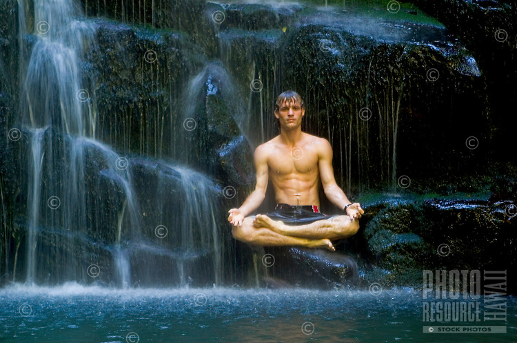 Man relaxes in meditation position under a waterfall.