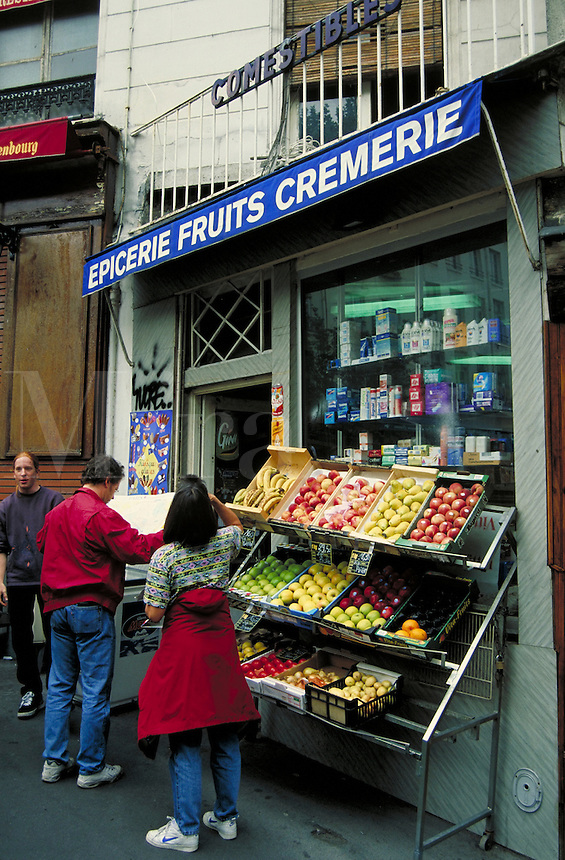 Tourists outside Latin Quarter produce shop on rue de la Montagne Ste. Genevieve. Flats of fruits and vegetables on sidewalk rack and drugstore items in window. Man reads Paris map. Paris, France.