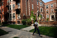 a woman passes by the entrance of a red Brick apartment building  in Hyde Park where Senator Barack Obama, the 2008 democratic presidential candidate and his family lived before buying their home in Kenwood..the image was taken on Tuesday August 5 2008 in Chicago, Illinois, United States.