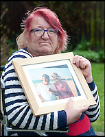 BNPS.co.uk (01202) 558833<br /> Picture: LauraJones/BNPS<br /> <br /> Pamela Young pictured with a photo of her son Andrew Young who is with BBC weather presenter Carol Kirkwood.<br /> <br /> Andrew Young, 40, became embroiled in an argument with Victor Ibitoye after he blasted him for riding his bike on the pavement.Just seconds after the altercation Mr Young was approached by Mr Ibitoye's friend, Lewis Gill, who launched a horrific attack on the Asperger's Syndrome sufferer.Shocking CCTV footage shows Gill, aged 20, throw a punch at Mr Young that was so forceful he was flung off the pavement and onto the road, striking his head.The callous thug is then seen walking away from the man as he lay lifeless on the ground.He was rushed from the scene in Bournemouth, Dorset, to Southampton General Hospital in Hampshire where he died the next day.A post mortem found no injuries to suggest that the vulnerable victim had tried to defend himself.Gill pleaded guilty to one count of manslaughter at Salisbury Crown Court and was jailed for four years and six months.