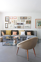 The wall of the living room above a long sofa upholstered in grey linen is lined with signed lithographs and framed sketches