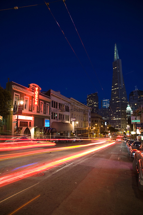 Street view of San Francisco at night with cars racing by and electric bus wires overhead.  The Transamerica Pyramid is the tallest and possibly the most recognizable skyscraper in the San Francisco skyline.