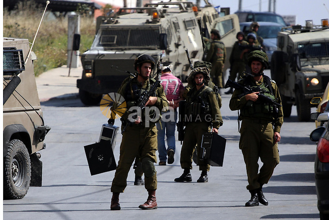 Israeli army forces carry seized computers during a raid in the West Bank city of Ramallah on May 30, 2011. Five Palestinians were arrest, three from the village of Amrine, near the northern West Bank city of Nablus and two others, from the area around Ramallah, Palestinian security sources said.Photo by Issam Rimawi