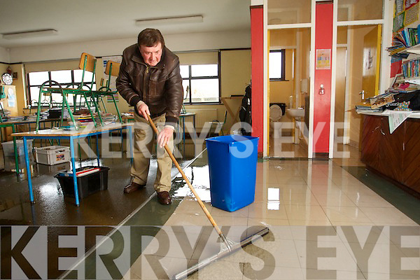 Jim Sullivan Caretaker of Scoil Mhic Easmainn mopping out the school after pipes burst over Christmas.