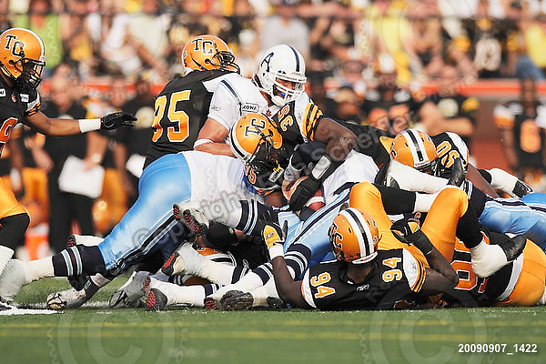 September 7, 2009; Hamilton, ON, CAN; Hamilton Tiger-Cats linebacker Otis Floyd (35) tries to strip the ball from Toronto Argonauts quarterback Cody Pickett (3). CFL football - the Labour Day Classic - Toronto Argonauts vs. Hamilton Tiger-Cats at Ivor Wynne Stadium. The Tiger-Cats defeated the Argos 34-15. Mandatory Credit: Ron Scheffler.