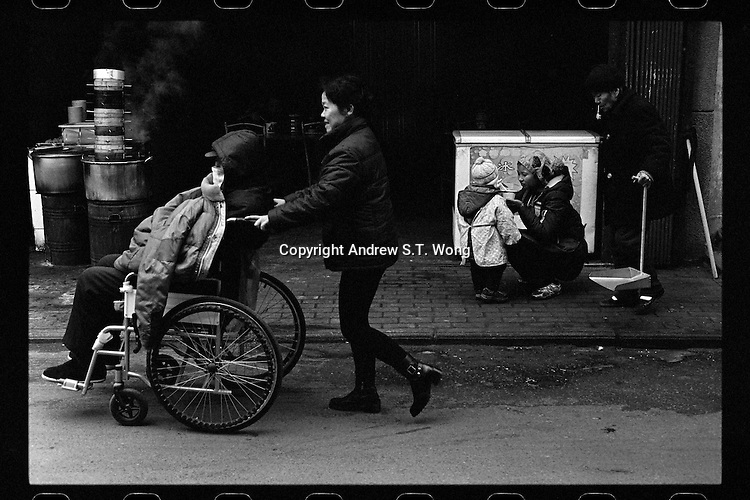 A woman pushes an old man on a wheelchair as a mother tries to feed her son outside a restaurant at a wet market in Wuhan, Hubei province, December 2011.