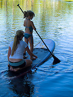 A mother teaches her daughter how to standup paddleboard on the calm pond of Richardson's Ocean Park in Hilo, Big Island.
