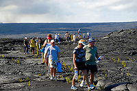 the first visitors make their down the Hawaii, USA county public viewing trail, near a large lava flow from Royal Gardens subdivision flowing into the ocean, Waikupanaha ocean entry, Kilauea volcano, east of Hawaii, USA Volcanoes National Park, Big Island of Hawaii, USA