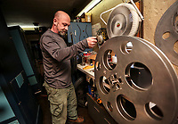 March 12, 2019. Encinitas, CA. USA| Owner Allen Largent uses a motor rewind bench to rewind a 35mm Rocky Horror Picture Show film at his La Paloma Theater in Encinitas.  | Photos by Jamie Scott Lytle. Copyright.