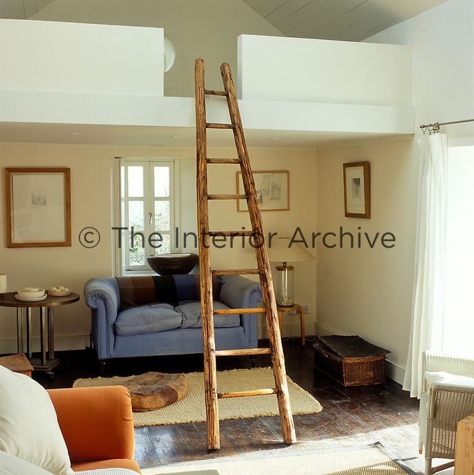 A rustic ladder ascends to a newly-created gallery bedroom above the main living area of this small cottage