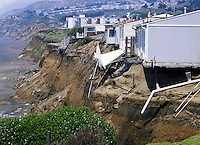 sandy bluff of coastline eroding under houses. erosion. Pacifica California.