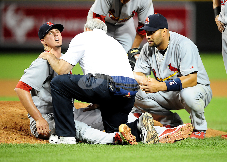 Apr. 12, 2011; Phoenix, AZ, USA; St. Louis Cardinals first baseman Albert Pujols (right) looks on as a trainer tends to injured pitcher Bryan Augenstein against the Arizona Diamondbacks in the seventh inning at Chase Field. Mandatory Credit: Mark J. Rebilas-