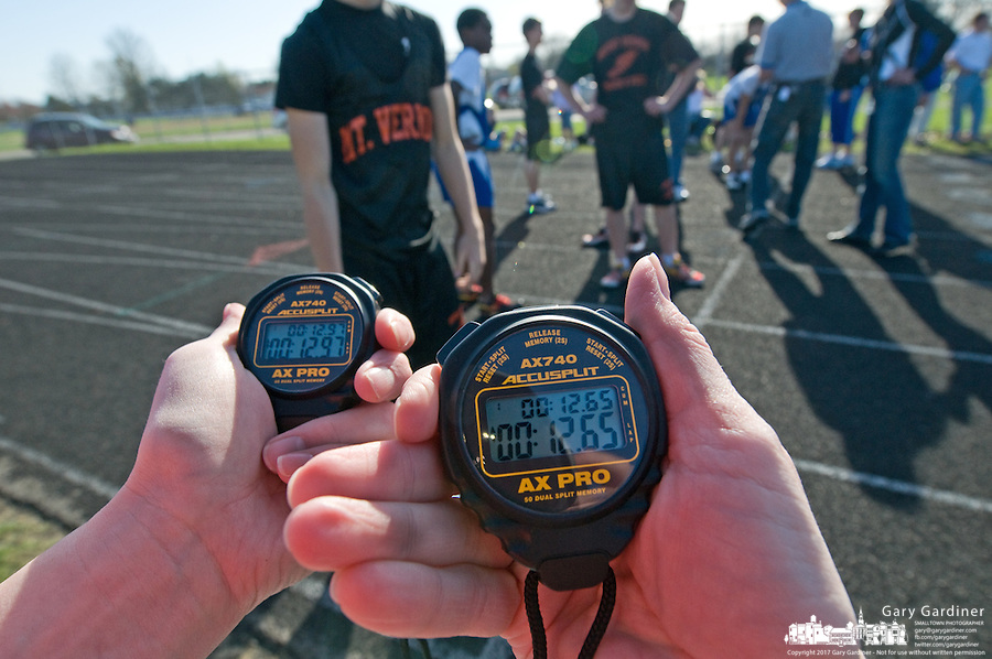 Judges check their stop watches at the finish line of a high school track meet.
