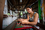 Siang Muan weaves cloth on a traditional loom in Kalay, a town in Myanmar.