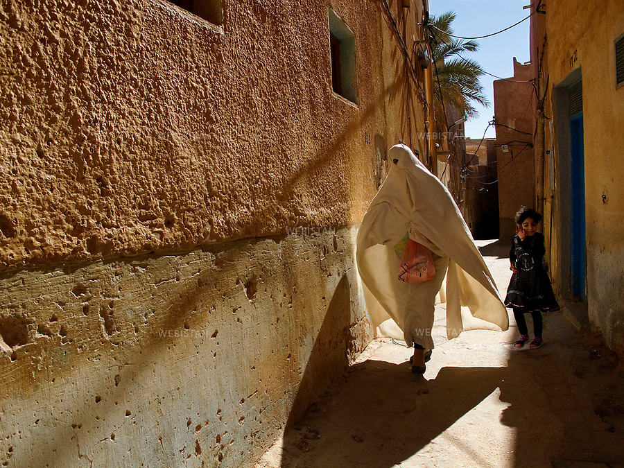 Algerie. Village de Bounoura. 9 Janvier 2012...Au detour d'une ruelle de la commune de Bounoura, dans la peripherie de Ghardaia , une femme porte le haik, un tissu blanc traditionnel tenu d'une main qui ne laisse entrevoir qu'un ?il. ..Algeria. Bounoura village. January 9, 2012...At the turn of an alley in the municipality of Bounoura, in the outskirts of Ghardaia, a woman carries the haik a traditional white cloth held in one hand, suggests just one eye...