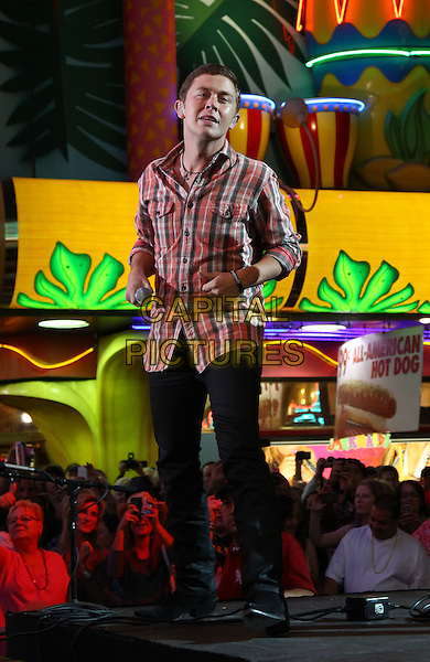 Scotty McCreery performs at 2012 ACM Weekend on Fremont Street Expereince, Las Vegas, Nevada, USA, .30th March 2012..music concert gig live on stage full length  red tartan plaid checked shirt microphone .CAP/ADM/MJT.© MJT/AdMedia/Capital Pictures.