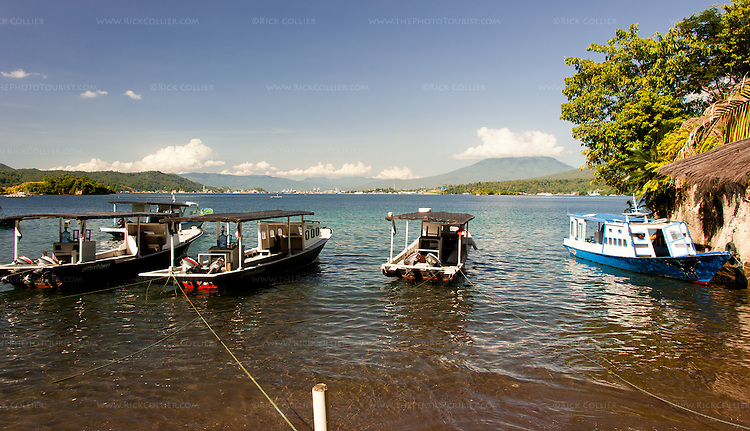 The Lembeh Resort's fleet of dive boats are moored in line, in front of the pool area and lawn at the Lembeh Resort, on Lembeh Island, off North Sulawesi, Indonesia.