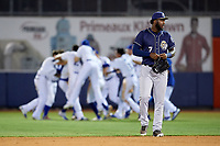 San Antonio Missions right fielder Franmil Reyes (7) walks off the field as the Tulsa Drillers celebrate their walk-off win during a game on June 1, 2017 at ONEOK Field in Tulsa, Oklahoma.  Tulsa defeated San Antonio 5-4 in eleven innings.  (Mike Janes/Four Seam Images)