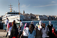 View from behind of people waiting for the ferry across the Bosphorus, Istanbul, Turkey. The Galata Tower rises above the skyline on the opposite shore. Picture by Manuel Cohen.