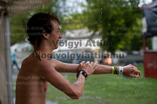 A participant cleans himself in rain water on Sziget festival held in Budapest, Hungary on August 07, 2011. ATTILA VOLGYI