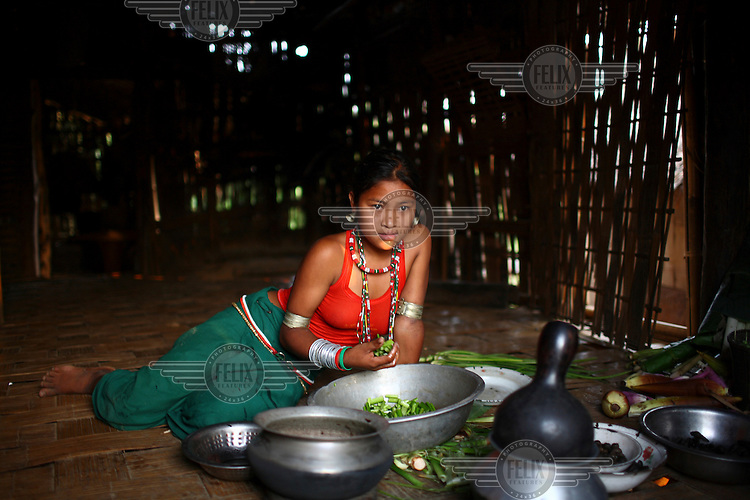 A young Mro (Mru) girl prepares a meal in her village in the Chittagong Hill Tracts.