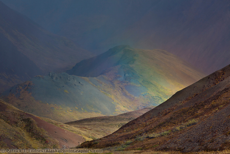 Rainbow over a stream drainage in the Alaska Range mountains in Denali National Park, Alaska.