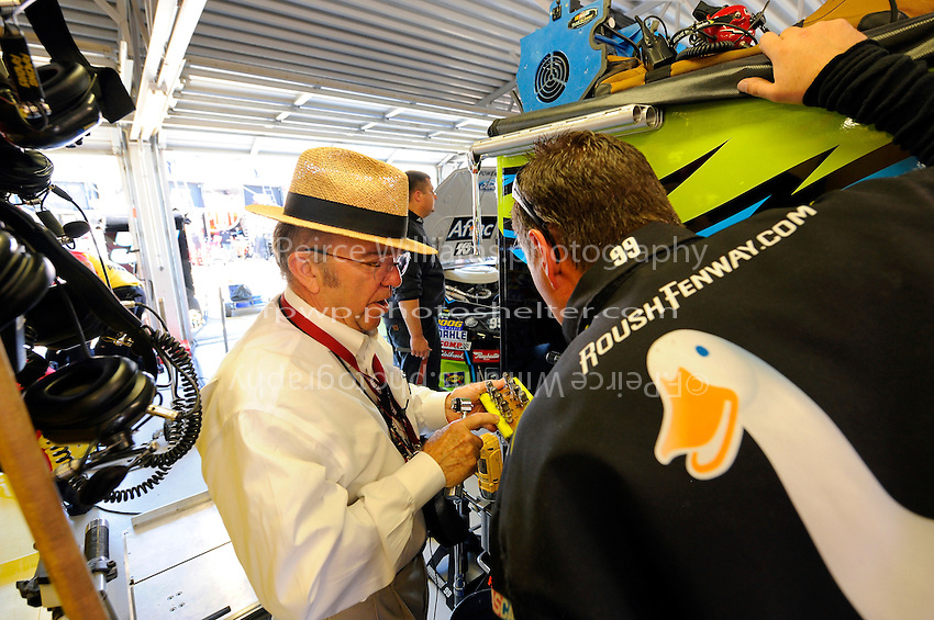 Jack Roush inspects spark plugs in the garage.