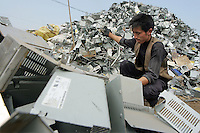 A junk yard worker sorts scraps of old computers and electronic trash in Guiyu, China March 9, 2005. For years, developed countries have been exporting tons of electronic waste to China for inexpensive, labor-intensive recycling and disposal.